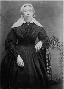 Vrouw in modejapon met lange muts ca 1880.