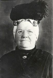 Vrouw met oorijzer,kanten muts en hoed.